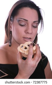 Beautiful brunette with artistic makeup eating a muffin