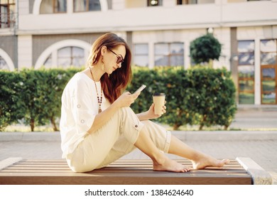 Beautiful brunette barefoot young woman sitting with cup of paper coffee on wooden bench and using mobile phone in summer, city lifestyle.