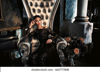 Beautiful brunette in bkack dress sitting on throne in royal interior