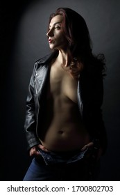 beautiful brunette in the black leather jacket and a jeans on a naked body