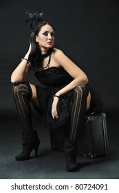 Beautiful brunette in a black outfit sitting sideways on a suitcase