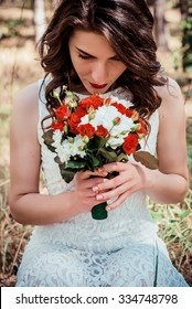 beautiful brunette bride with a bouquet of red roses and white daisy