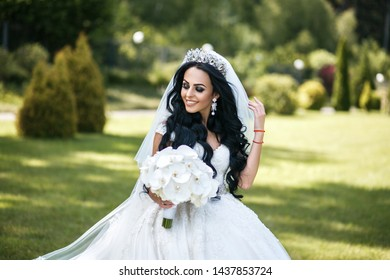 Beautiful brunette bride in a crown with make-up smoky eyes posing in a park. She holds flowers in her hand and looks away with a smile.