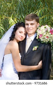 a beautiful brunette bride embraces a groom with love