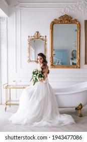 Beautiful brunette bride posing in white dress with wedding bouquet in studio