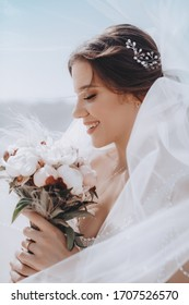 Beautiful brunette bride with stylish make-up in white dress in spring nature