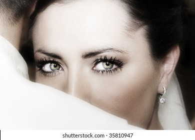 Beautiful brunette bride wearing diamond jewelery looking over the grooms shoulder