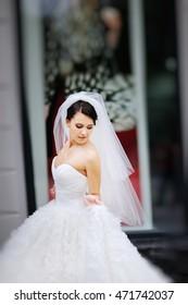 Beautiful brunette bride wearing white dress walking street