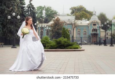 beautiful brunette bride in white wedding dress hold her bridal bouquet made from white roses and dance on city park background