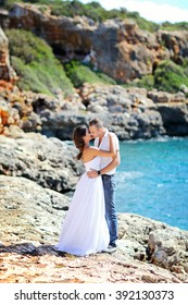 Beautiful brunette bride in white wedding dress and blond groom, together in sunshine on a  beach. Blue sea and  rock in the background. Wedding and summer vacation concept.