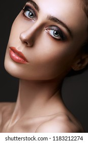 Beautiful brunette with bright make-up smoky eyes, thick eyebrows, pink lips. Evening look