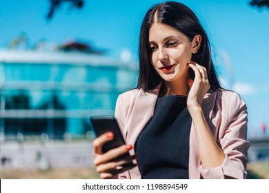 Beautiful brunette business woman wearing smart black dress, sunglasses standing near hi-tech glass building of business center checking message on her mobile phone. Copy space for your text.