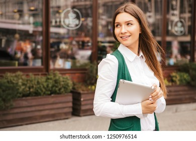 Beautiful brunette business woman in white blouse and green jacket working on a tablet in her hands outdoors. Freelancer in european city. Space for text
