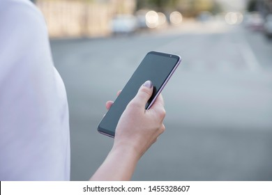 Beautiful brunette business woman in white skirt and grey suit trousers working on a mobile phone in her hands outdoors. European city on background. copy space