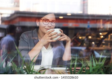 Beautiful brunette business woman in white skirt and grey suit jacket working from the cafe. She wears glasses and drink a cup of coffee. copy space