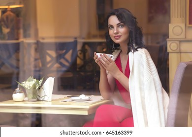 Beautiful brunette caucasian business woman sitting in cafe on her coffee break in red  casual but a bit classic dress and white cardigan, smiling. Copy space. Rich luxury place. Evening, sunset light
