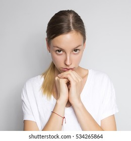 Beautiful brunette caucasian woman in white blouse with bright emotions standing on a neutral grey background. Her hands make a gesture. She serious, praying