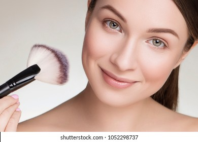 Beautiful brunette caucasian young woman prepare herself, applying powder on her cheeks with a brush. Clean, fresh, natural, flawless skin. Soft smile on her face. Close up on a neutral background
