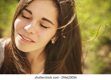 Beautiful brunette caucasian young woman laughing showing perfect teeth on summer sunny day. outdoors. nature. copy space