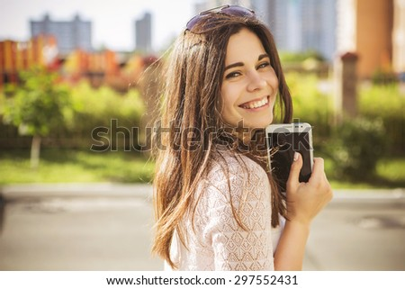 47a866e0ff Beautiful brunette caucasian young woman laughing showing perfect teeth on  summer sunny day with white phone