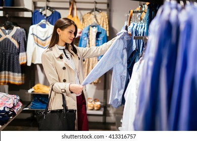 Beautiful brunette choosing and  buying clothes