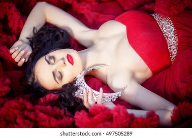 Beautiful brunette in a crown with a bouquet in his hand and in a chic big and lush red dress in the park among the green