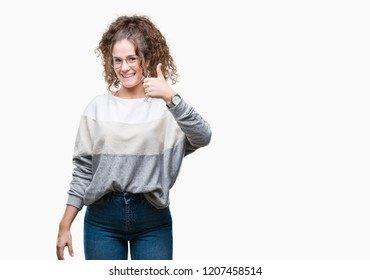 Beautiful brunette curly hair young girl wearing glasses over isolated background doing happy thumbs up gesture with hand. Approving expression looking at the camera with showing success.