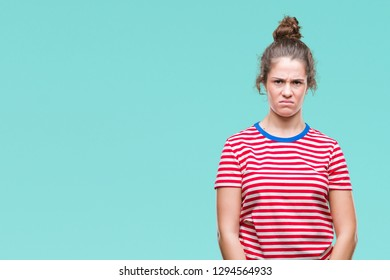 Beautiful brunette curly hair young girl wearing casual look over isolated background skeptic and nervous, frowning upset because of problem. Negative person.