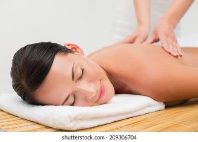 Beautiful brunette enjoying a back massage in the health spa