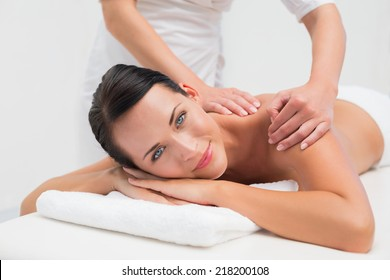 Beautiful brunette enjoying a back massage smiling at camera in the health spa