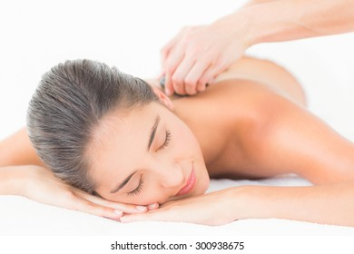 Beautiful brunette enjoying a hot stone massage at the health spa