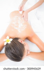 Beautiful brunette enjoying a salt scrub treatment at the health spa