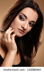 Beautiful brunette with evening makeup over brown background
