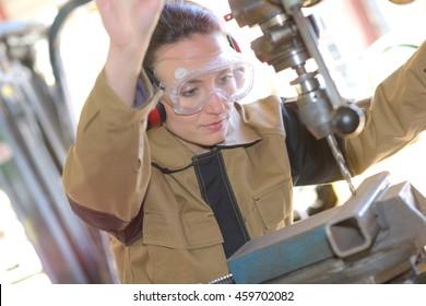 beautiful brunette factory worker drilling a piece