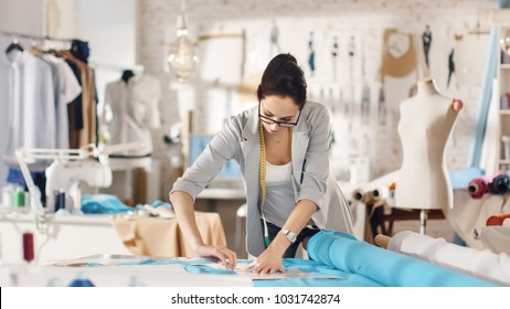 Beautiful Brunette fashion, designer,  Lays Out Templates on the fabrics and Looks at Her Smartphone. She Works in a Light Colorful Studio Full of Various Clothes, Fabrics and Sketches on the Wall.