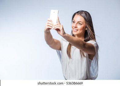 Beautiful brunette female business / professional model talking, texting, taking a selfie on her smart phone in a studio on white background