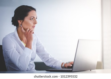 Beautiful brunette female business woman working on her laptop in her office
