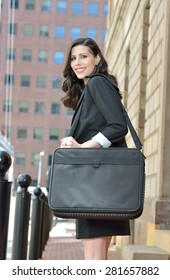 Beautiful brunette female  business woman carrying briefcase looks back as she steps off curb