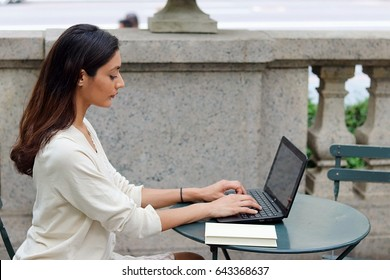 Beautiful brunette female concentrating typing on laptop computer in white dress while sitting outside urban park table with city background side view