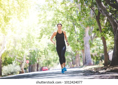 Beautiful brunette female fitness model running / stretching / exercising outside in a leafy and green suburb