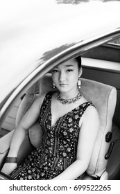 Beautiful brunette female model inside a vintage car