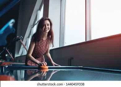 beautiful brunette female playing air hockey with friend