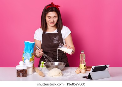 Beautiful brunette female pours milk into plate. Chef kneads dough, preparing for Easter holiday, making hot cross buns. Pink background. Concept of cooking food and baking cakes. Copy space.