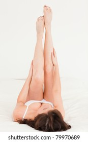 Beautiful brunette female stretching her legs while lying on a bed
