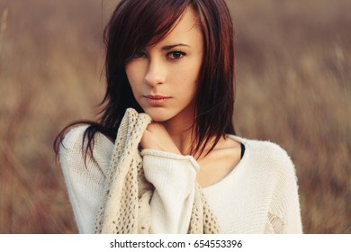 Beautiful brunette in a field freezing with the scarf.