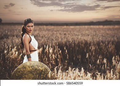 Beautiful brunette girl among grass in meadow holding iron shield in hand and looking at camera. Woman with long hair wearing in white dress like greece style. Wife waiting husband after war.