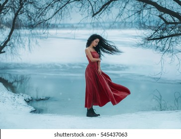 Beautiful brunette girl badly frozen. Background shore of a frozen river, water and ice. She is dressed in a beautiful red dress. The wind waves are long, curly hair. Fantasy photo, creative color.
