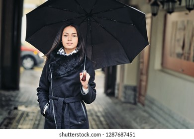 Beautiful brunette girl in black clothes with umbrella - close up portrait