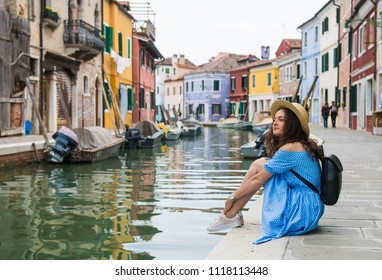 Beautiful brunette girl in blue dress and hat sitting on the edge of water canal in Burano, Venice