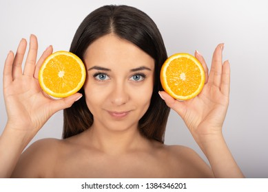beautiful brunette girl, blue eyes, in her hand an orange, white background, close-up